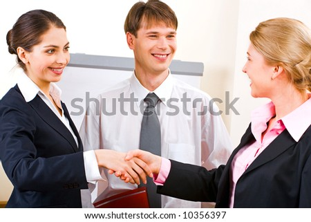 Portrait of two successful businesswomen shaking hands at meeting while businessmen looking at them with smile - stock photo