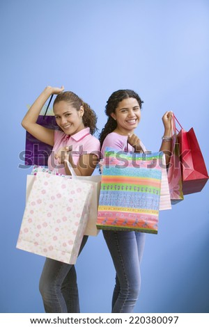 Portrait of two teenage girls holding gift bags - stock photo