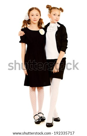 Portrait of two ten years schoolgirls wearing uniform. Isolated over white. - stock photo