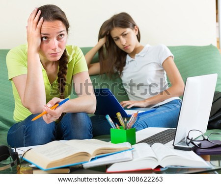 Portrait of two tired girls with laptops and books at home. Selective focus - stock photo