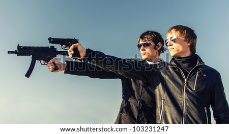 Portrait of two tough guys with guns - stock photo