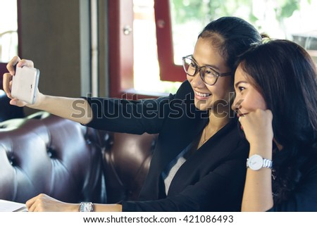 Portrait of two woman taking selfie at cafe together - stock photo