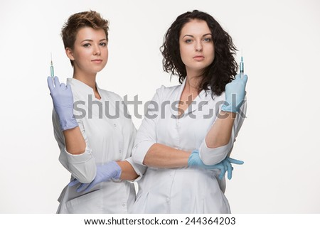 Portrait of two women surgeons showing syringes - stock photo