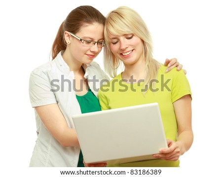 Portrait of two women viewing laptop isolated on white background. - stock photo