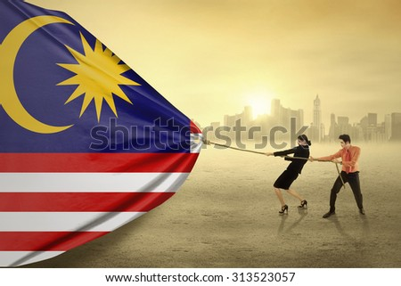 Portrait of two young asian people pulling a flag of malaysian, shot outdoors - stock photo