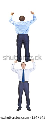 portrait of two young businessman -  one businessman in full growth picks up on the other hand lifting it up over her head up - stock photo