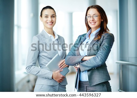 Portrait of two young businesswomen colleagues in an office - stock photo