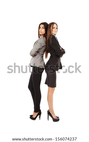 Portrait of two young businesswomen standing back to back isolated on white background - stock photo