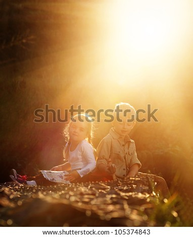 Portrait of two young children sitting together in the sunlight outdoors. brother and sister siblings - stock photo