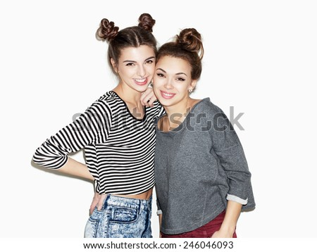 Portrait of two young girl standing together and smiling.  - stock photo