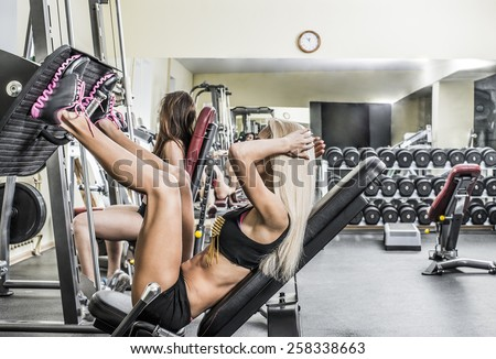 Portrait of two young Girls do exercise for legs and hands. in fitness gym on mirror with reflection and window background 2 woman with long blond and brown hair sitting No face Unrecognizable person  - stock photo
