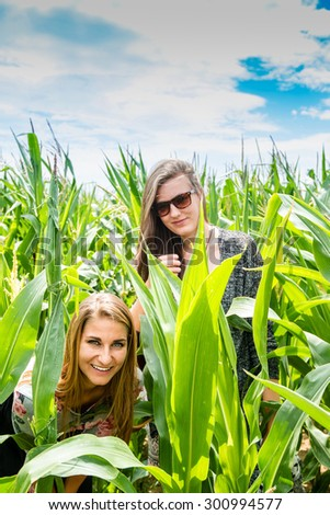 Portrait of two young girls hiding in a green cornfield, playing hide and seek in nature. - stock photo