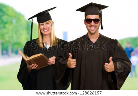 Portrait Of Two Young Graduate People, Outdoors - stock photo
