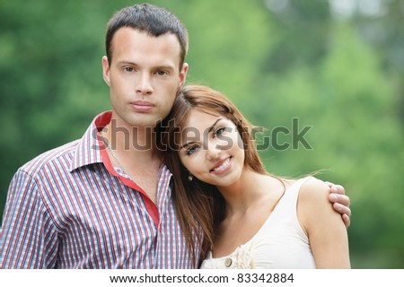 Portrait of two young happy lovers at summer green park. - stock photo