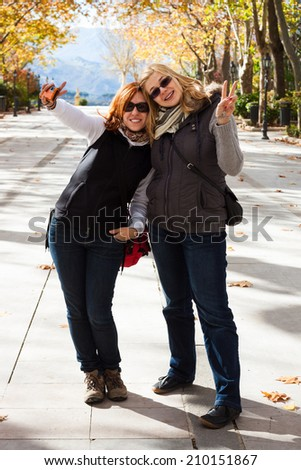 Portrait of two young happy women in park - stock photo