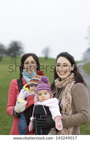 Portrait of two young mothers with their babies in park - stock photo