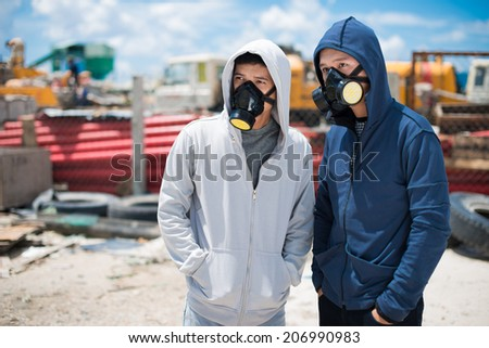 Portrait of two young people in respirators standing outdoors - stock photo