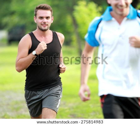 portrait of two young sport man jogging together at roadside - stock photo