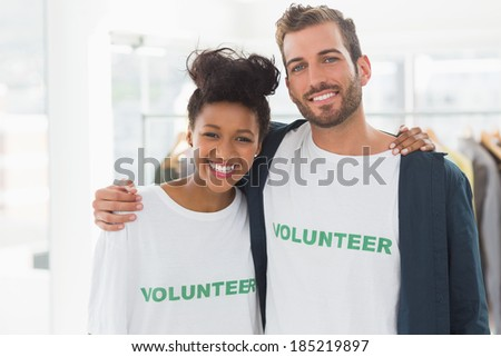 Portrait of two young volunteers with arms around standing indoors - stock photo