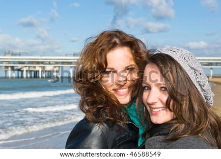 Portrait of two young women on the beach on a beautiful autumn afternoon - stock photo