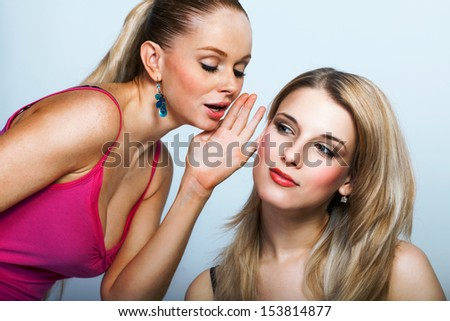 Portrait of two young women sharing secret  - stock photo