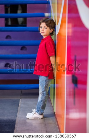 Portrait of unhappy little boy standing against wall in kindergarten - stock photo