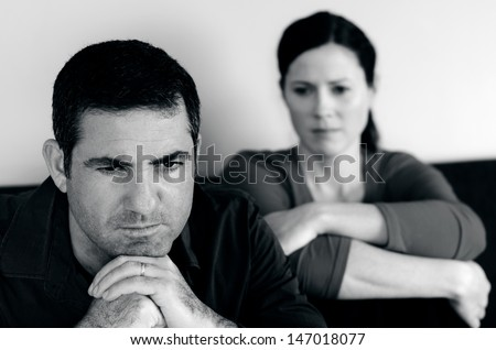 Portrait of unhappy young couple who have fallen out over a disagreement sitting on a sofa. Man in the front and the woman in the background.(BW) - stock photo