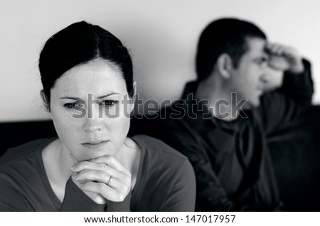 Portrait of unhappy young couple who have fallen out over a disagreement sitting on a sofa. Woman in the front and the man in the background.(BW) - stock photo