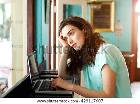 Portrait of university student with laptop looking out of window - stock photo