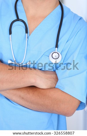 Portrait of unknown male surgeon doctor holding his stethoscope - stock photo