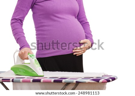 Portrait of unrecognizable pregnant housewife ironing on a white background - stock photo