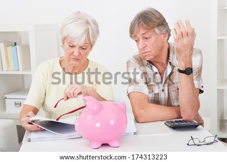 Portrait Of Upset Senior Couple Calculating Finance At Home - stock photo