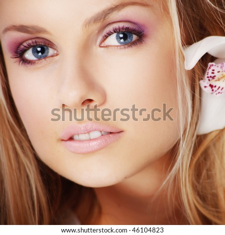 Portrait of very beautiful woman with orchid in her hair - stock photo