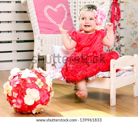 Portrait of very sweet little child sitting like a princess in funny pink and red costume - stock photo