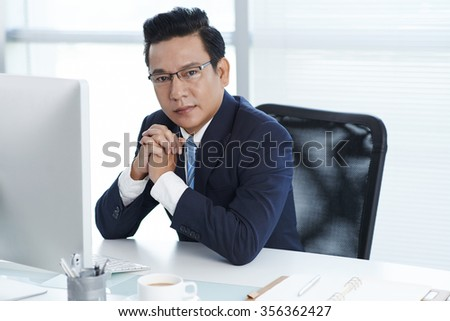 Portrait of Vietnamese entrepreneur sitting at his workplace - stock photo