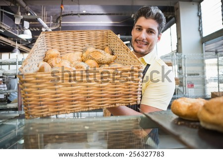 Portrait of waiter in apron showing basket of bread at the bakery - stock photo