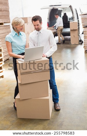 Portrait of warehouse manager and colleague using laptop - stock photo