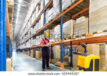 Portrait of Warehouse worker in a yellow helmet in a logistic center - stock photo