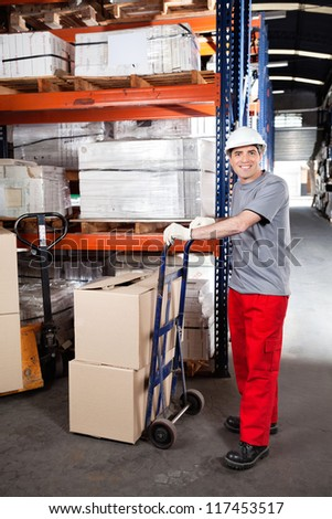 Portrait of warehouse worker with handtruck loading cardboard boxes at warehouse - stock photo