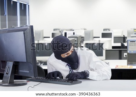 Portrait of watchful robber wearing balaclava while stealing information in the office room - stock photo