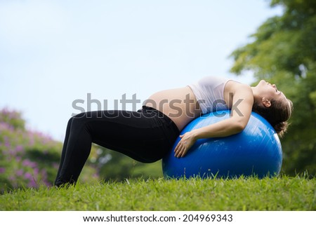 Portrait of white beautiful pregnant woman doing fitness exercise in park working out abs on fitness ball. Copy space - stock photo