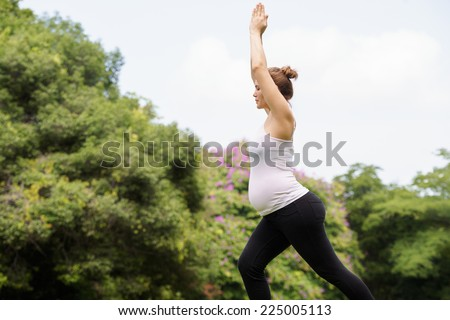 Portrait of white beautiful pregnant woman doing yoga exercise in park, with arms raised - stock photo