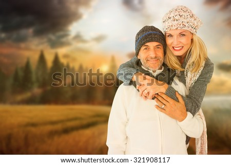 Portrait of wife embracing husband against country scene - stock photo