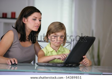 Portrait of woman and a little girl in front of a laptop computer - stock photo
