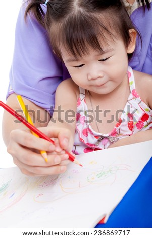 Portrait of woman and little asian girl drawing and painting together, mother teach her daughter to draw with colour pencil - stock photo