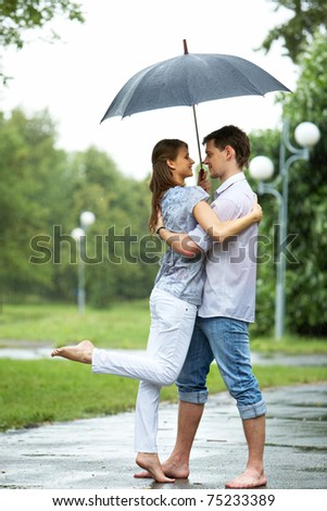 Portrait of woman and man embracing under umbrella during rain - stock photo