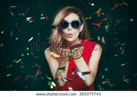 Portrait of woman blowing confetti - stock photo