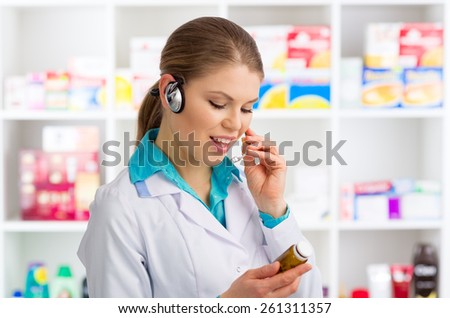 Portrait of woman doctor pharmacist in headset speaking in microphone. Young friendly female chemist working in drug store.  - stock photo
