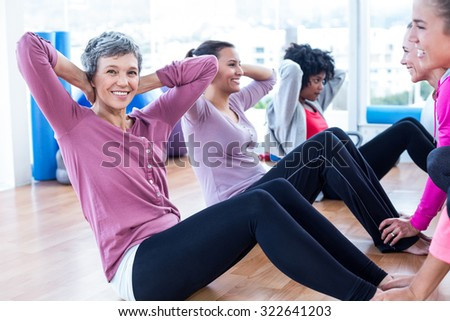 Portrait of woman doing sit ups with friends at fitness studio - stock photo