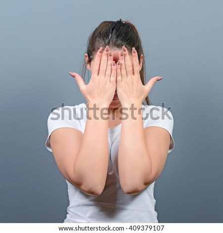 Portrait of woman hiding her face with both hands against gray background - stock photo